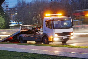 A tow truck sits by the side of the road with its lights on at dusk.